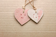 Couple of handmade cardboard hearts with drawn male and female characters against striped cardboard sheet Stock Photos
