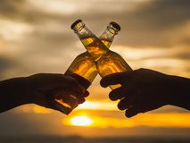 Couple hands holding beer bottles and clanging on the sunset beach. Party, Holiday, Summer, Friendship Concept. royalty free stock photography