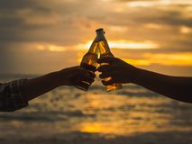 Couple hands holding beer bottles and clanging on the sunset beach. Party, Holiday, Summer, Friendship Concept. stock images