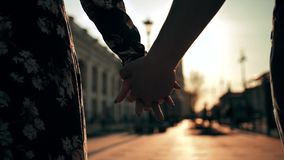 Couple hands holding each other on city street sunset light with beautiful lens flare. Male and female lovers touching their arms. Super slow motion shot stock footage
