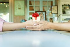 A couple hands holding a golden gift box with red ribbon in rest. Aurant Stock Image