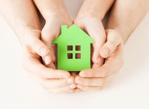 Couple hands holding green house. Closeup picture of women and men hands holding green house Royalty Free Stock Photos