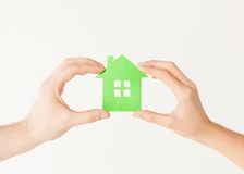 Couple hands holding green house. Closeup picture of women and men hands holding green house Royalty Free Stock Photo