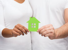 Couple hands holding green house. Real estate, family and eco concept - closeup picture of couple hands holding green house Royalty Free Stock Photo