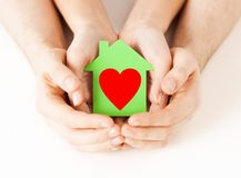 Couple hands holding green paper house Royalty Free Stock Image