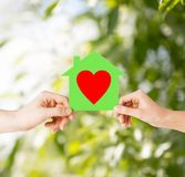 Couple hands holding green paper house Stock Photo
