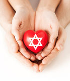 Couple hands holding heart with star of david stock images