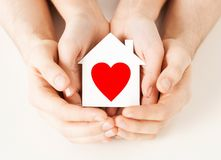 Couple hands holding white paper house Stock Images