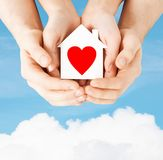Couple hands holding white paper house Stock Photos