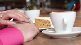 Couple hands near a coffee cup and cake stock video footage