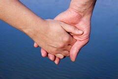 Couple hands over blue lake Stock Image