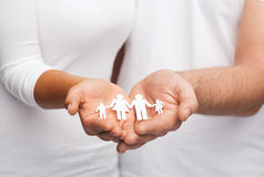 Couple hands with paper man family Stock Images