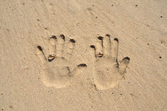Couple hands print on sand with wedding rings Stock Photography