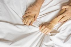 Couple hands pulling white sheets in ecstasy, orgasm. Concept of passion. Oorgasm. Erotic moments. Intimate concept. Sex. Couple. Bedroom. Hotel room. Spa royalty free stock photo