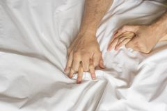 Couple hands pulling white sheets in ecstasy, orgasm. Concept of passion. Oorgasm. Erotic moments. Intimate concept. Sex. Couple. Bedroom. Hotel room. Spa stock images