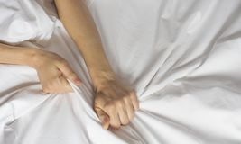 Couple hands pulling white sheets in ecstasy, orgasm. Concept of passion. Oorgasm. Erotic moments. Intimate concept. Sex. Couple. Bedroom. Hotel room. Spa stock photography