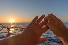 Couple hands with rings, hands with wedding rings, overlooking t. He sunset in the sea Stock Image