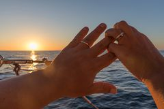 Couple hands with rings, hands with wedding rings, overlooking t. He sunset in the sea Stock Photo