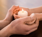 Couple hands. Young couple are holding hands and candle on the table Royalty Free Stock Image