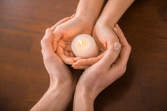 Couple hands. Young couple are holding hands and candle on the table Stock Photo