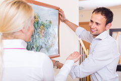 Couple hanging art picture in frame Stock Images