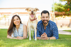 Couple hanging out with their dog. Cute young couple relaxing and spending some time with their dog at a park Royalty Free Stock Images