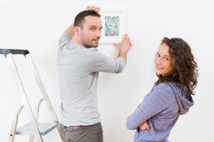 Couple hanging a painting in their new flat Stock Photography