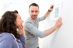 Couple hanging a painting in their new flat Royalty Free Stock Photography