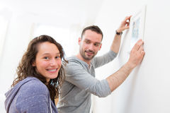 Couple hanging a painting in their new flat Royalty Free Stock Image