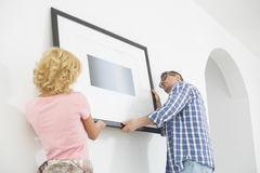 Couple hanging picture frame on wall in new house Royalty Free Stock Images