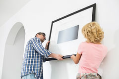 Couple hanging picture frame on wall in new house Royalty Free Stock Photography
