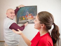 Couple hanging picture on wall at. Focus on girl stock photography