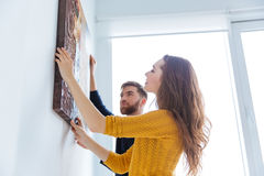 Couple hanging picture on the wall Royalty Free Stock Photo