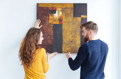 Couple hanging picture on the wall at home stock photo