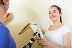 Couple hanging shelf at home Royalty Free Stock Photo