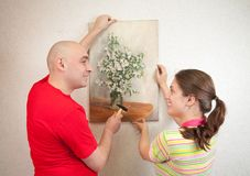 Couple hanging up an art picture on their wall Stock Photos