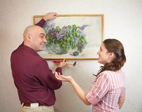 Couple hanging up an art picture on their wall Royalty Free Stock Photo