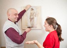 Couple hanging up an art picture on their wall Stock Images