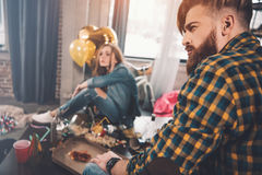 Couple with hangover sitting in messy room Stock Photography