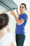 Couple hangs curtains  on window Stock Images