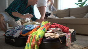 A couple is haphazardly packing and trying to close a chock-full suitcase. Time lapse. stock footage