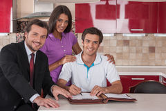 Couple of happy buyers signing agreement on new house. Royalty Free Stock Images