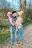 Couple with happy daughter kissing in the forest Stock Photography
