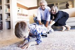 Couple of happy grandparents are fun nephew with skateboard. In a modern apartment Royalty Free Stock Photo