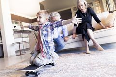 Couple of happy grandparents are fun nephew with skateboard. In a modern apartment Stock Photos