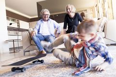 Couple of happy grandparents are fun nephew with skateboard. In a modern apartment Stock Photo