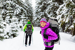 Couple happy hikers trekking in winter woods Royalty Free Stock Image