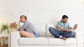 Couple with happy husband using internet app on digital tablet pad ignoring bored and sad wife Stock Images