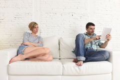 Couple with happy husband using internet app on digital tablet pad ignoring bored and sad wife Royalty Free Stock Photo