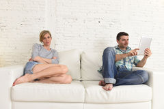 Couple with happy husband using internet app on digital tablet pad ignoring bored and sad wife Stock Photo
